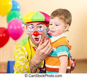 joyful kid with clown on birthday party