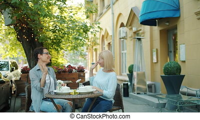 Joyful ladies chatting then doing high-five in outdoor cafe...