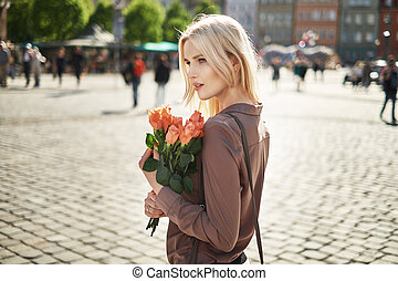 Joyful lady holding a bouquet of fresh roses