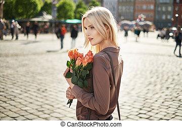 Joyful lady holding a bouquet of fresh roses