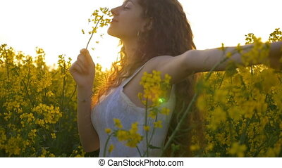 Joyful lady in white dress spinning in the rapeseed field holding a yellow flower in one hand
