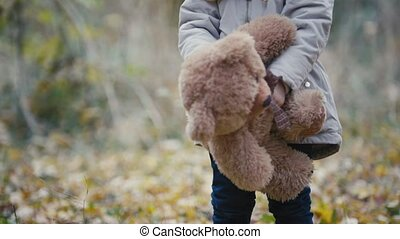 Joyful little blonde girl plays with teddy bear in autumn park