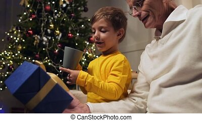 Joyful little boy and his grandfather having fun while...