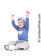 Joyful little boy sitting with arms raised and laughing -...