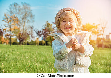 Joyful little caucasian child girl walks in the park and claps her hands