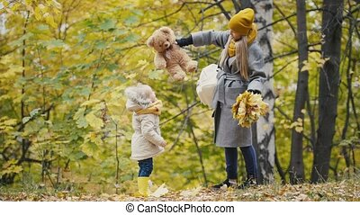 Joyful little daughter with her mommy and Teddy the Bear...