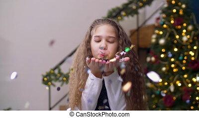 Joyful little girl blowing out confetti from palms - Joyful...