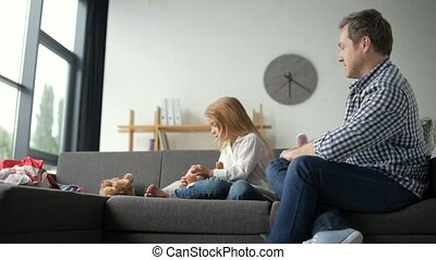 Joyful little girl enjoying time with her father at home -...