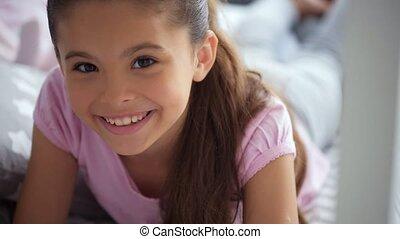 Joyful little girl lying in her bed