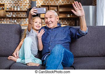 Joyful little girl making selfies with her grandfather
