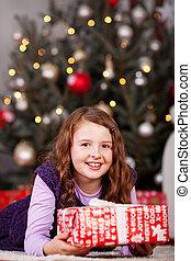 Joyful little girl with a Christmas gift