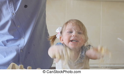 Joyful little girl with dad in the kitchen playing with flour, slow motion.