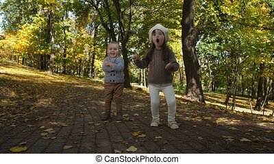 Joyful little siblings dancing funny on park alley