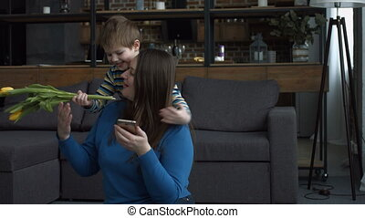 Joyful little son giving flowers to his mother