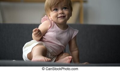 Joyful little toddler sitting on the couch at home