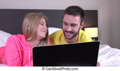 Joyful lovers using laptop lying on bed at home, online shopping