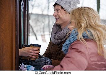 Joyful loving couple purchasing coffee in park store