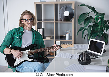 Joyful male guitarist performing music in office
