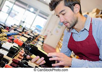 joyful male seller holding bottle wine in wine shop