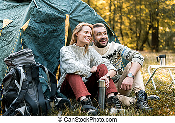 Joyful man and woman relaxing in forest