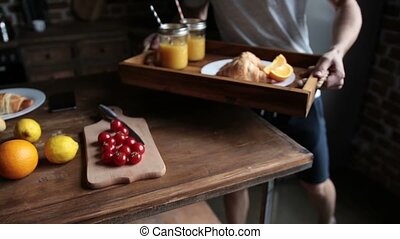 Joyful man bringing breakfast to woman in bed