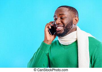 Joyful man communicating on mobile phone