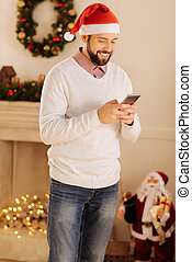 Joyful man in Santa hat reading text messages