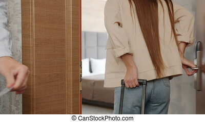 Joyful man is opening hotel door with key card entering room kissing and hugging wife, couple are carrying suitcases. Travelling and relationship concept.