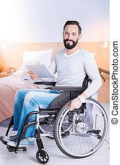 Joyful man sitting I a wheelchair with a tablet