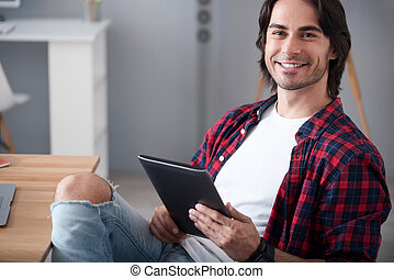 Joyful man using tablet