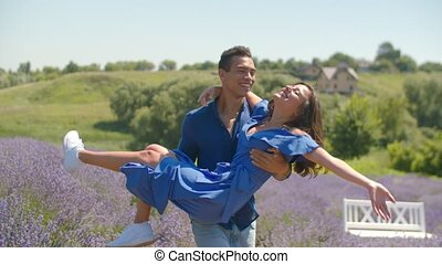 Joyful man whirling beloved woman in floral field - Carefree...