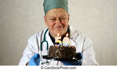 Joyful mature adult doctor in medical mask and white robe, blows out number 50 candles on birthday cake. Make a wish. On light background. Close-up.