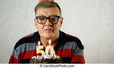 Joyful mature adult man wearing blue eyeglasses blows out number 50 candles on birthday cake. Make a wish. On light background. Close-up.