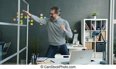 Joyful mature businessman dancing having fun relaxing indoors in office