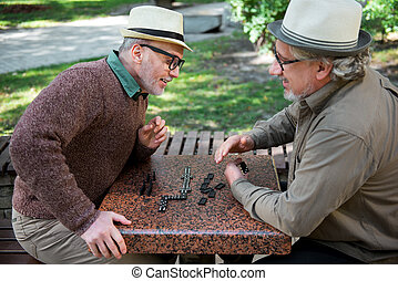 Joyful mature friends relaxing with intellectual game outdoor