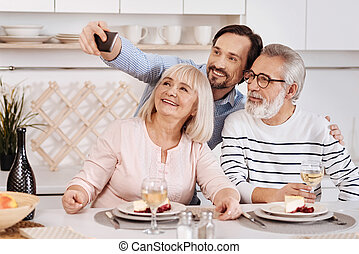 Joyful mature man taking selfie with aged parents at home