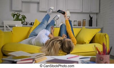 Joyful mom and daughter taking selfie on couch