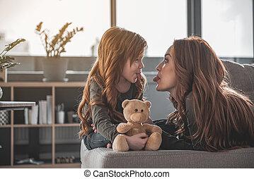 Joyful mom and kid fooling around at home