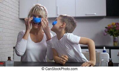 Joyful mom and son sticking handmade slime on face - Cute...
