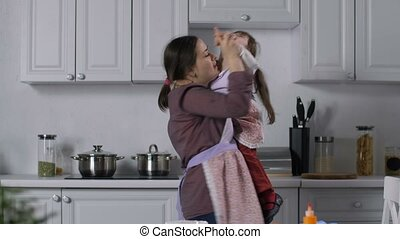 Joyful smiling mother holding her adorable preschool daughter with down syndrome relaxing in the kitchen dancing. Positive mom with special needs child enjoying leisure in rhythm of dance indoors.