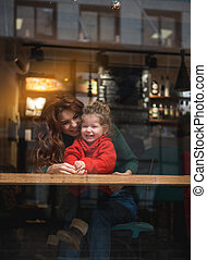 Joyful mom playing with her daughter in cafe