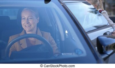 Joyful mom taking girl home after school by car