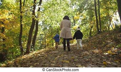Joyful mom with children running through park