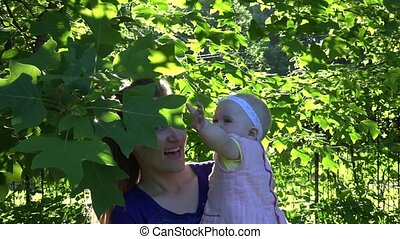 Joyful mommy with infant daughter have fun between tulip tree branches. 4K