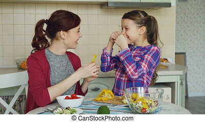 Joyful mother and cute cheerful daughter have fun grimacing silly with vegetables while cooking in the kitchen at home. Family, cook, and people concept