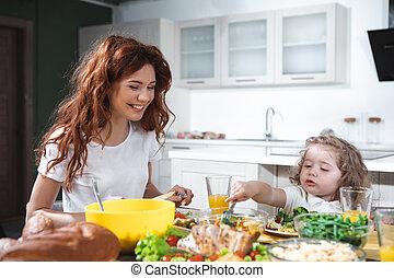Joyful mother and daughter enjoying healthy dinner together