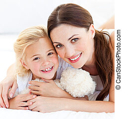 Joyful mother and her little girl playing together on a bed