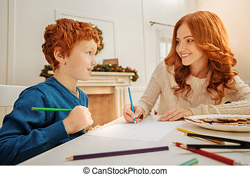 Joyful mother and son drawing with colorful pencils together