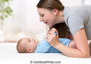 joyful mother playing and doing gymnastics her baby infant
