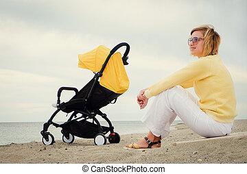 Joyful mother relaxing with sleeping baby in stroller